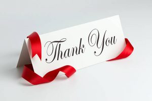 Thank you note with red ribbon over white background